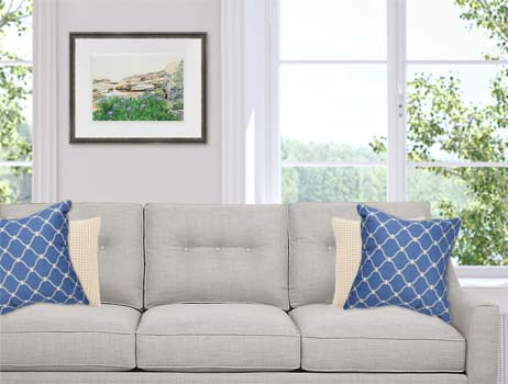 Watercolor painting of purple Irises on the rocky shore in Maine framed over a gray sofa