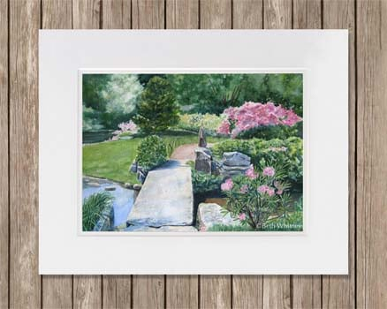 Stone Bridge in a garden with pink rhododendrons and azaleas